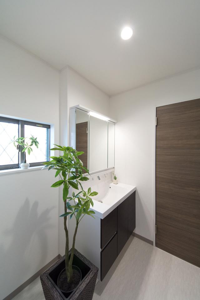 洗面化粧台扉は、ダークブラウン系の色でアクセント、清潔感のあるサニタリールーム。