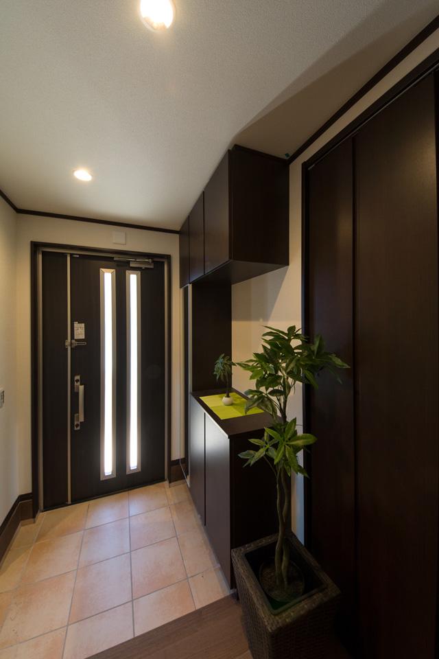 スリット窓が入った大きな玄関ドアとダークブラウンの玄関収納が玄関スペースに深みを与えます。