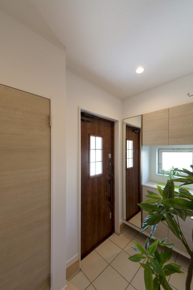 カントリー調の玄関ドアは室内のナチュラルなテイストにマッチし、窓の自然光が温かみをプラスします。
