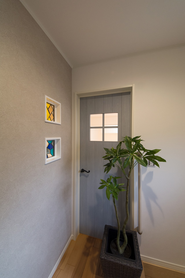 小窓のついたリビングドアとステンドグラス前は、いつも必ず通る場所。癒しの空間となりました。