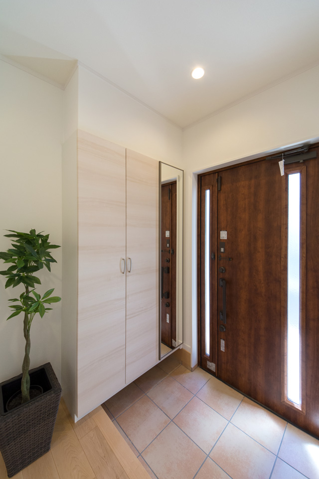 玄関ドアのガラス部分から差し込む光とベージュのテラコッタ調タイルが温かみのある空間を演出。