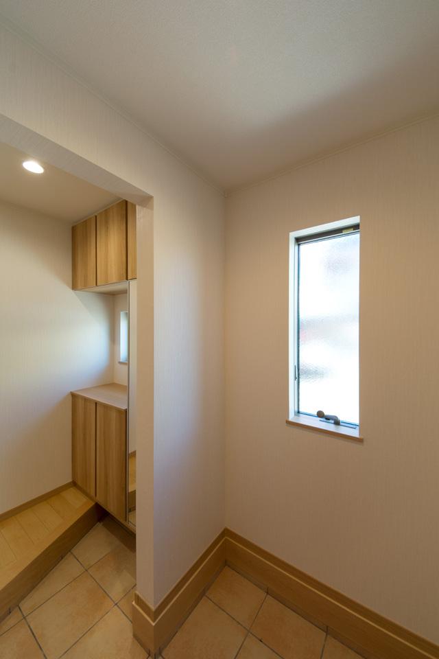 窓の自然光とナチュラルな配色でやさしくリラックスできる玄関ホール。