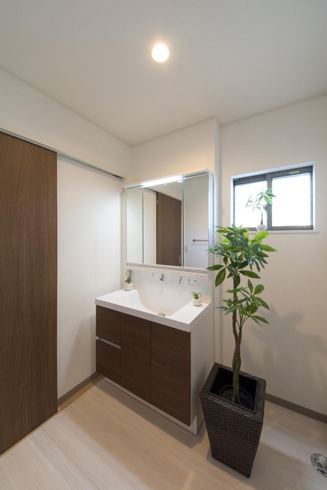 洗面化粧台扉をクリエモカ色でアクセント、ナチュラルで落ち着いた印象のサニタリールーム。