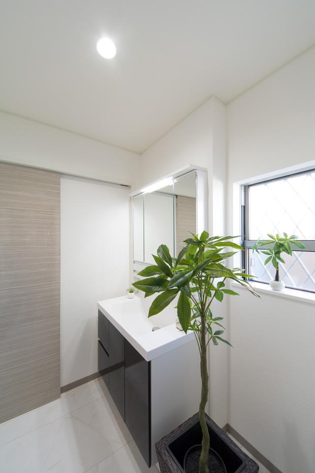 白を基調とした清潔感のあるサニタリールーム。洗面化粧台扉はディープグレーでアクセント。