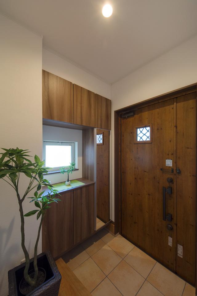 木の温もり感じる玄関ドアと収納、テラコッタ調タイルが相まってナチュラルな雰囲気を演出。