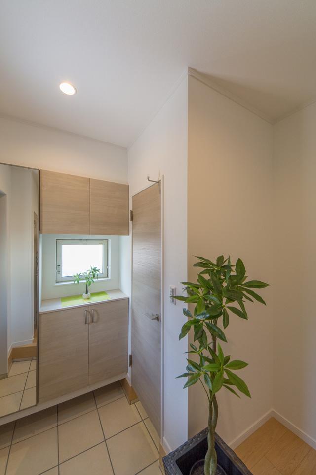 シューズクロークのある便利な玄関。クリーミーな配色でやさしくリラックスできる空間に。