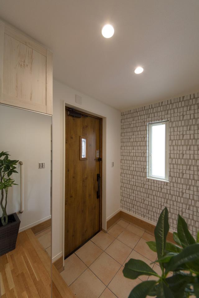 マキアートパインの玄関扉とベージュのテラコッタ調タイルがナチュラルな雰囲気を演出。