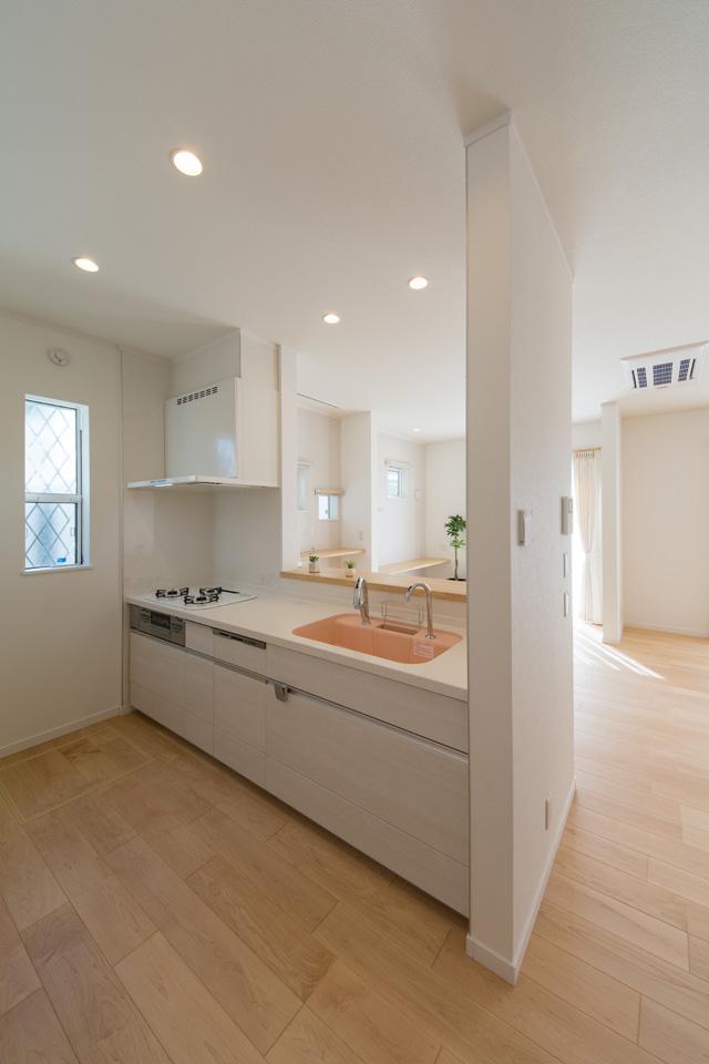 ホワイトベースの清潔感のあるキッチン。桜カラーのシンクが優しい印象を与えます。