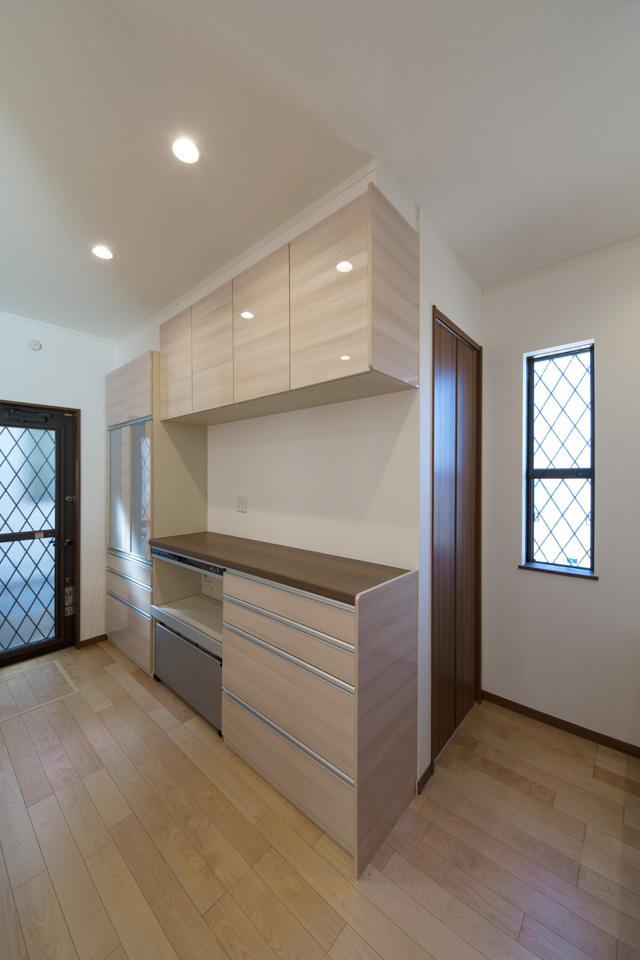 キッチン背面にはキッチンと同じ配色のカップボード。カップボード裏にはパントリーを設置。