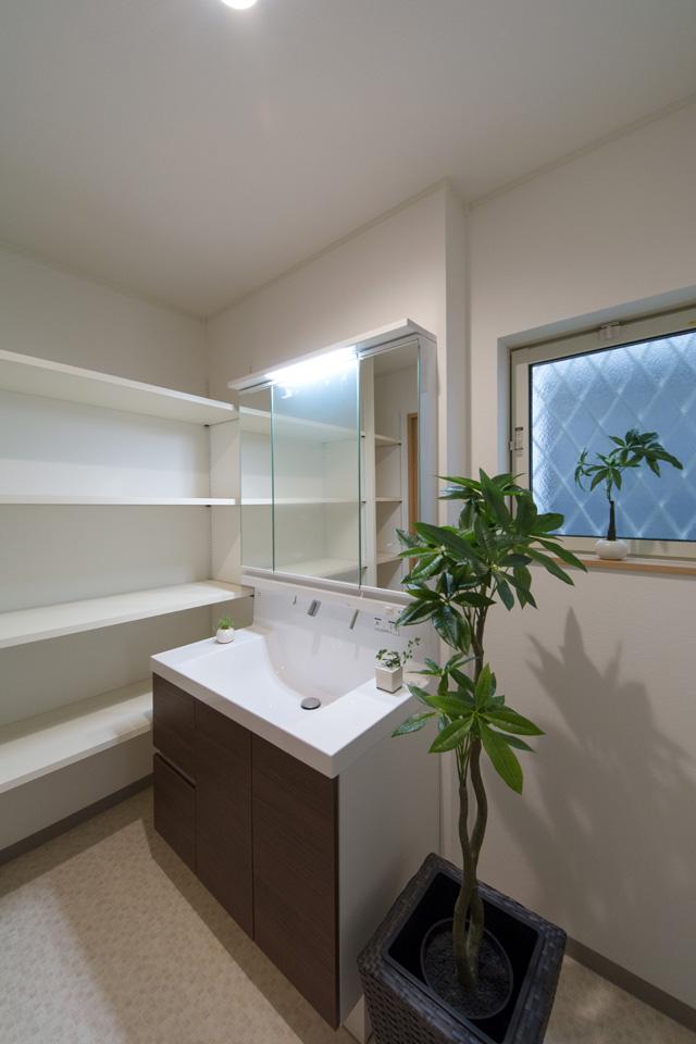 白を基調とした清潔感のあるサニタリールーム。洗面化粧台はモカ色でアクセント。