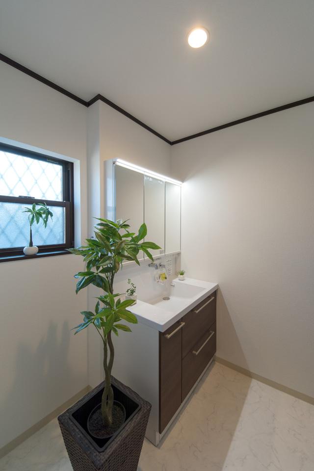 清潔感のあるサニタリールーム。洗面化粧台扉を、ダークブラウン系の色でアクセントにしました。