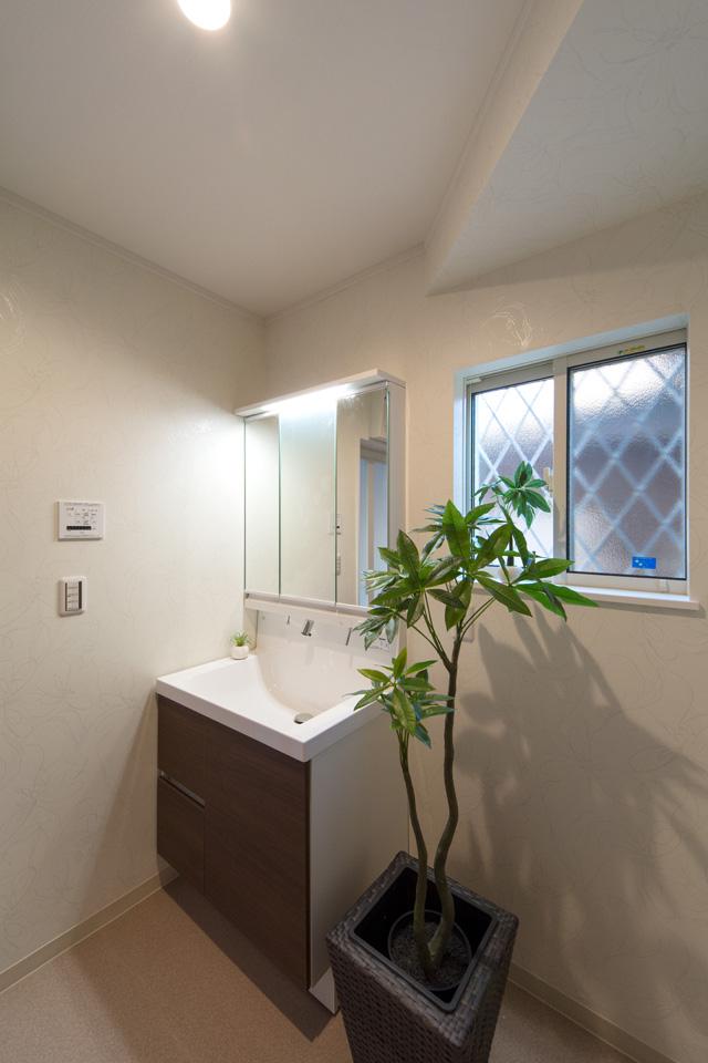 白を基調とした清潔感のあるサニタリールーム。ブラウンの洗面化粧台がナチュラルな雰囲気を演出。