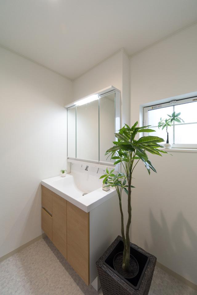 白を基調とした清潔感のあるサニタリールーム。ライトブラウンの洗面化粧台扉がナチュラルな雰囲気を演出します。