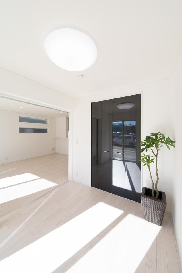美しく清潔感あるアッシュホワイトのフローリング。ブラックの鏡面扉との組合せがホワイトモダンな空間を演出します。
