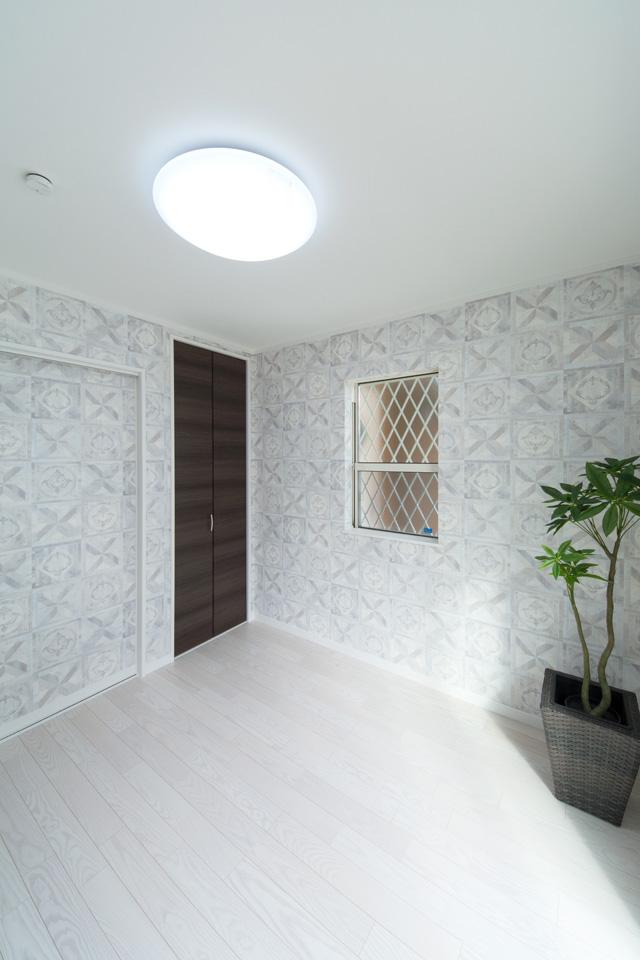 1F洋室。アッシュグレーのパターン柄アクセントクロスがスタイリッシュな空間を演出。