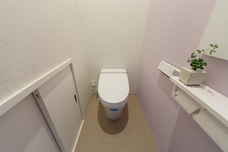 ライトピンクのアクセントクロスが爽やかな印象を与える1階トイレ。