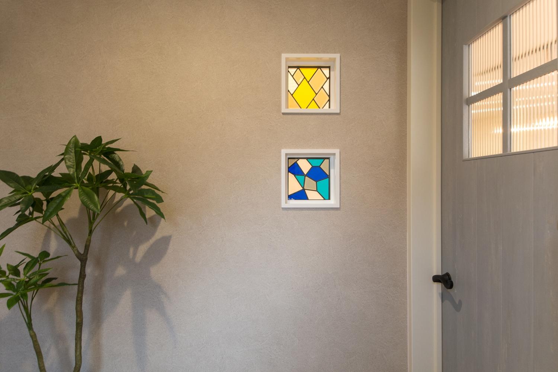 1F玄関ホールと階段前の間の壁に、ハンドメイドのステンドグラスを取り入れました。