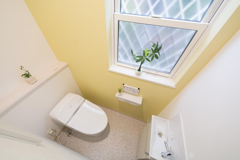 ライトイエローのアクセントクロスが印象的な1階トイレ。