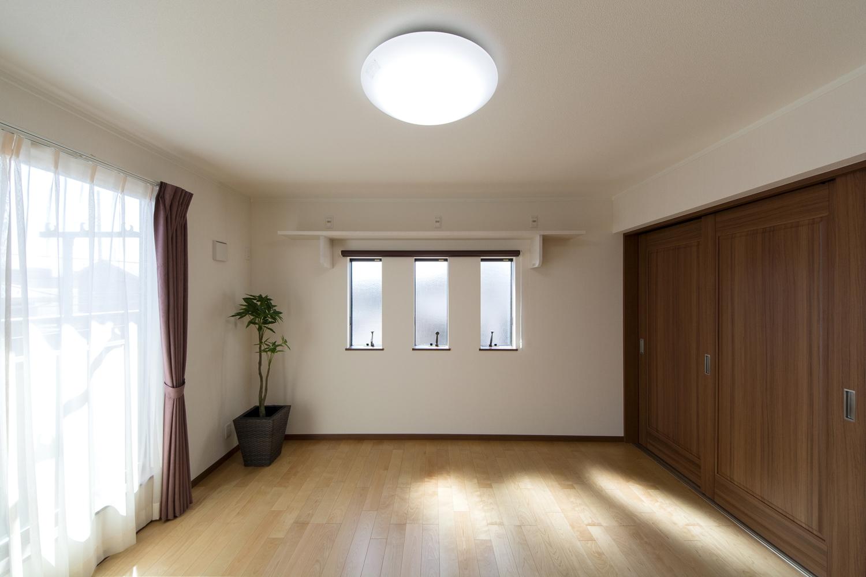 窓から自然光が入る明るい2F洋室。ブラウンの大きな3枚の引戸は端正な表情でモダンな印象を与えます。