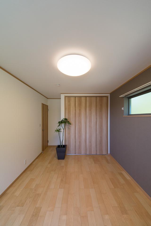 2F洋室。ブラウンのアクセントクロスが空間を引き締め、モダンな雰囲気を演出。