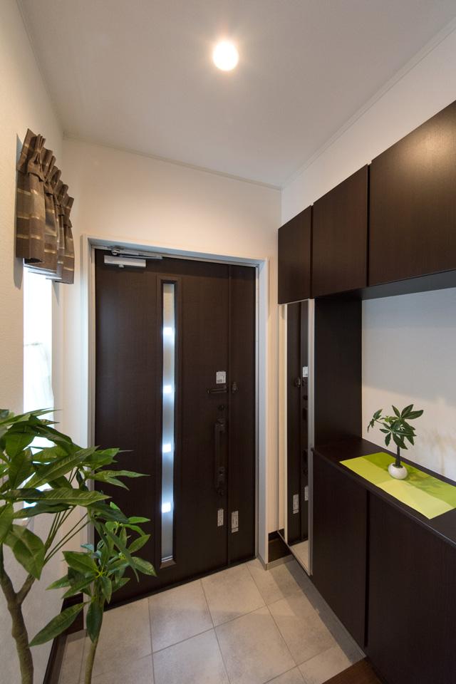 ダーク色の玄関扉と収納、グレーのテラコッタ調タイルがラグジュアリーな空間を演出。