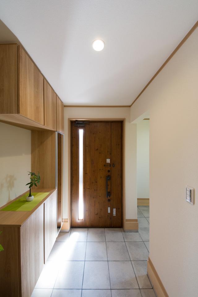 カントリーテイストの木目調玄関ドア。ガラス部分から光が差し込み明るい玄関ホール。