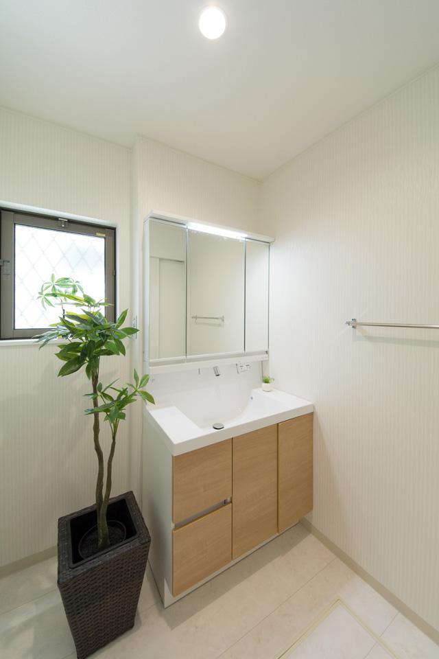 白を基調とした清潔感のあるサニタリールーム。木目調の洗面化粧台扉がナチュラルな雰囲気を演出します。
