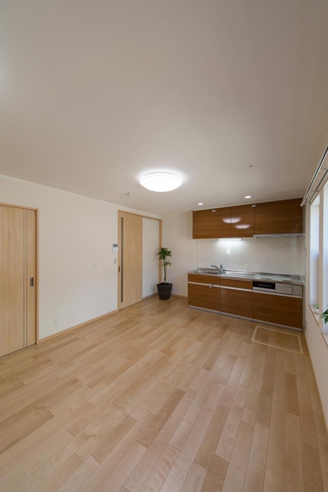 光沢のある木目調ブラウンのキッチン扉が、ナチュラルな雰囲気をプラス。