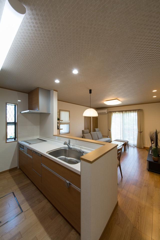 天然木の表情や色合いを表現したブラウン系扉カラーでナチュラルな印象の対面キッチンに大変身。
