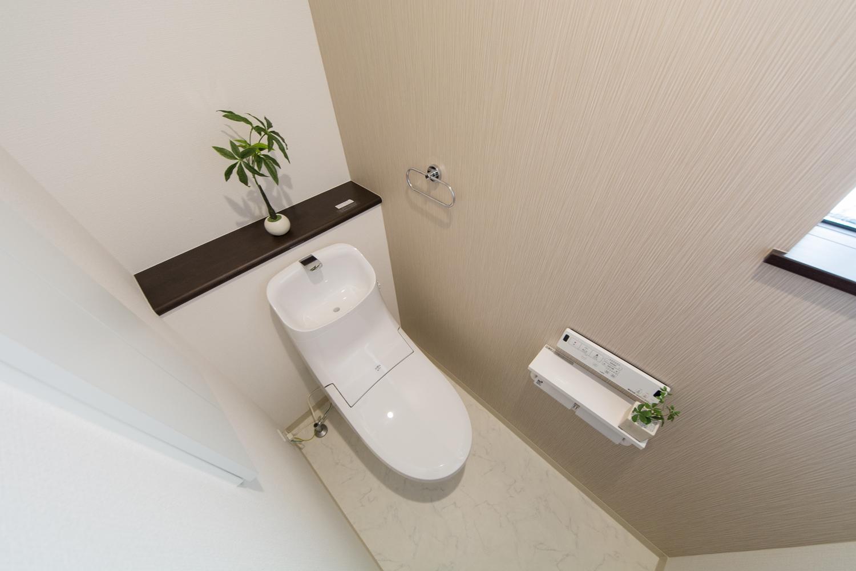 1Fトイレ。ベージュのアクセントクロスは抗菌効果があり、汚れに強く清潔で快適な空間。