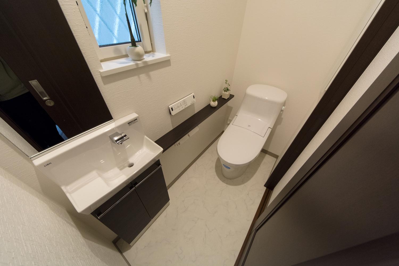 白を基調とした空間に、ダーク色の扉を配色した清潔で落ち着く空間の1Fトイレ。