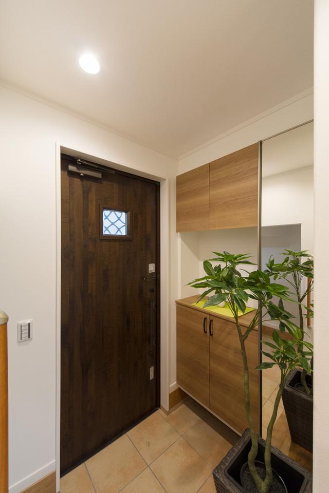 ココナッツブラウンの玄関扉とベージュのテラコッタ調タイルがナチュラルな雰囲気を演出。
