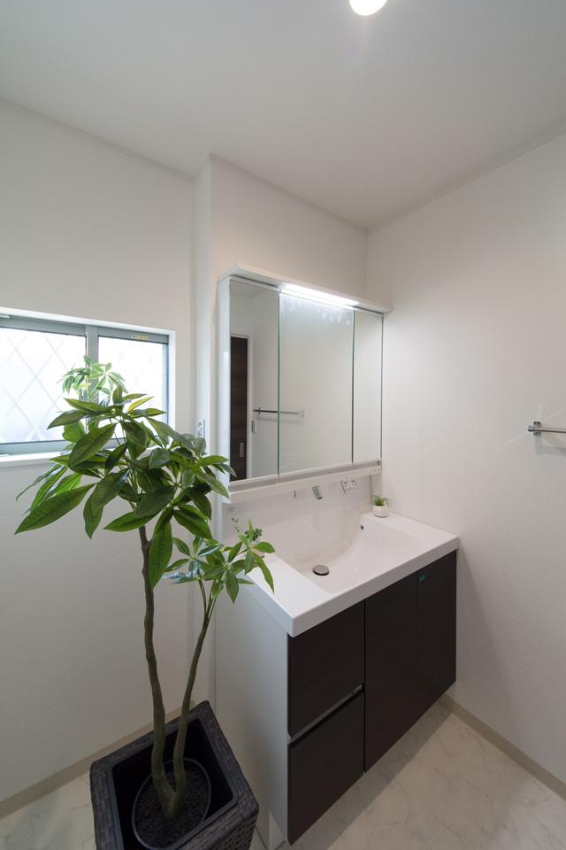 清潔感のあるサニタリールーム。洗面化粧台扉は、ダークブラウン系の色でアクセント。