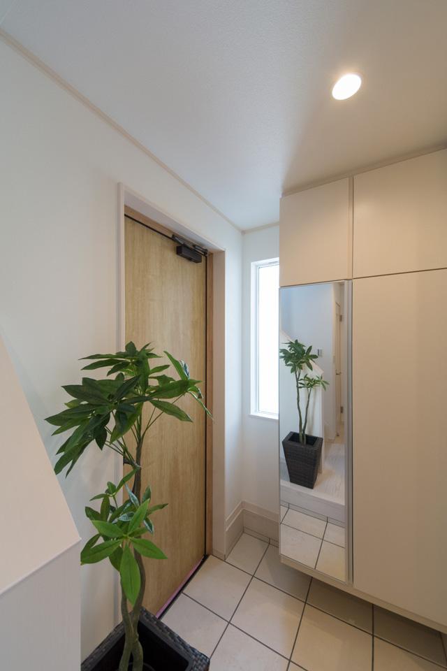 玄関ドア横の窓から自然光が差し込み、明るい空間に