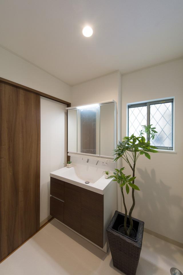 白を基調とした清潔感のあるサニタリールーム。モカ色の洗面化粧台がナチュラルな雰囲気を演出。
