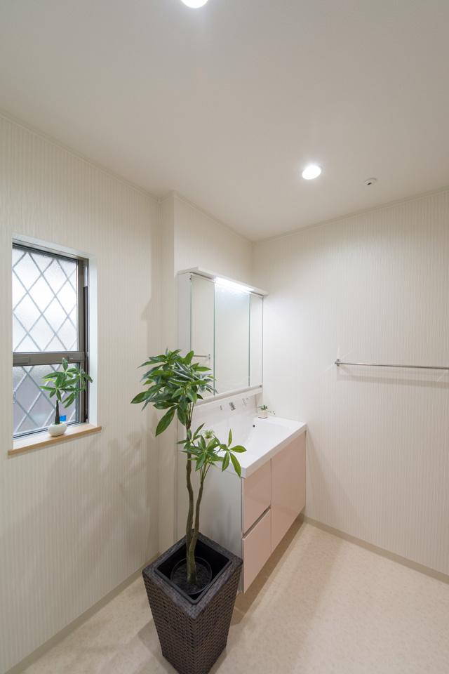 白を基調とした清潔感のある1Fサニタリールーム。ピンク色が可愛らしい洗面化粧台扉。