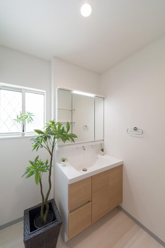 白を基調とした清潔感のあるサニタリールーム。木目調の洗面化粧台がナチュラルな空間を演出。