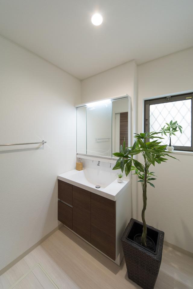 清潔感のあるサニタリールーム。洗面化粧台扉はダークブラウン色でアクセントをつけました。
