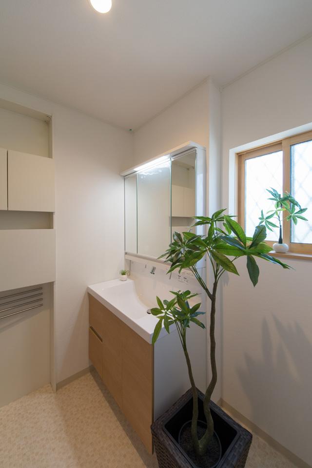 白を基調とした清潔感のあるサニタリールーム。木目調の洗面化粧台扉がナチュラルな空間を演出します。