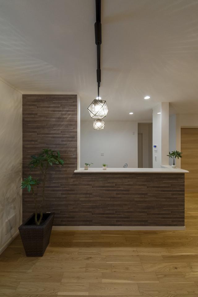 キッチン前のスタイリッシュなアクセントクロスに、ペンダントライトの陰影が雰囲気のあるダイニング空間を演出。