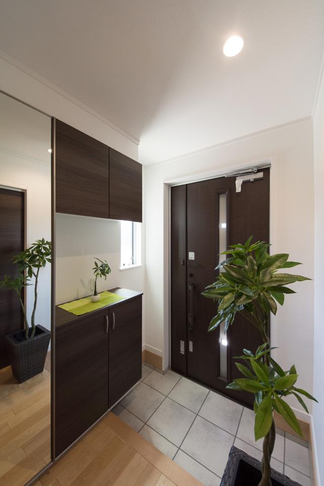 ダークブラウンン系の玄関ドアと収納が、モダンな空間を演出。