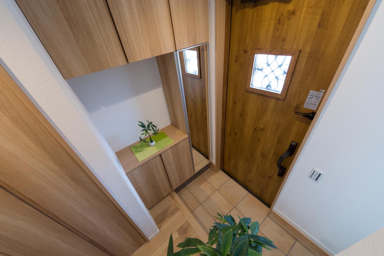 アンティーク調の玄関ドアと木の温もり感じる収納。