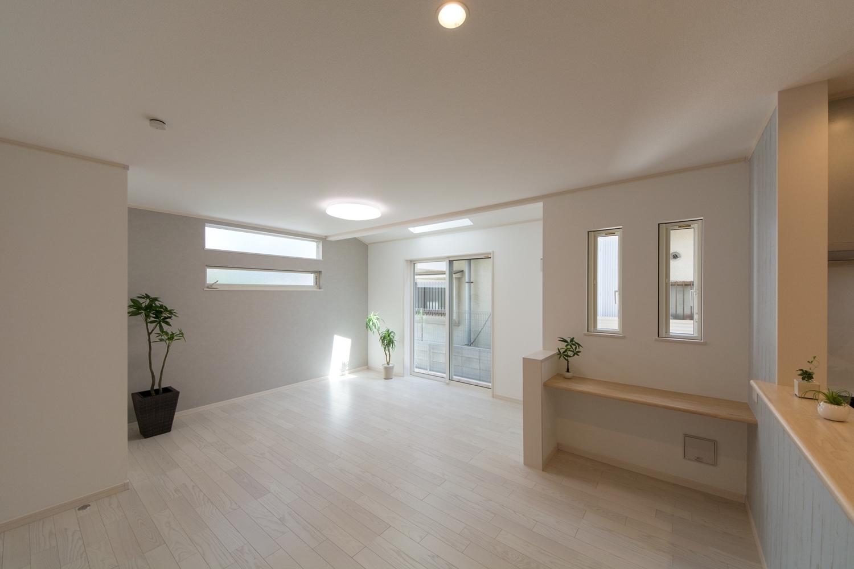 天井から明るい陽射しが入るリビングに、上品な白に囲まれた明るく開放的な空間
