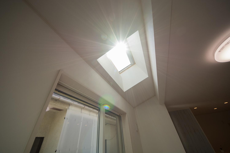 勾配天井のガラス部分から明るい陽射しが入るリビングは明るく開放感のある空間に。