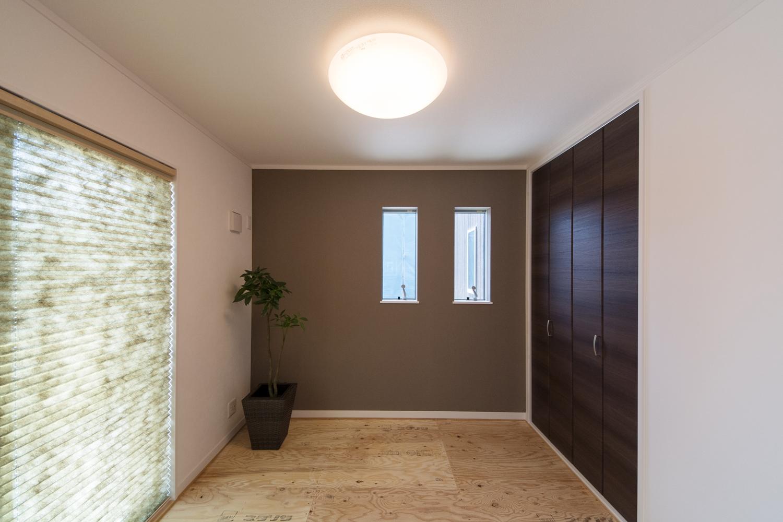 1F畳敷き洋室(写真は畳設置前)。ブラウンのアクセントクロスがモダンな空間を演出。