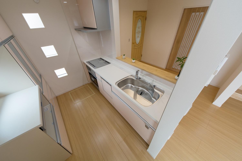 キューブ型の小窓と、ピンク色のキッチン扉が可愛らしくキッチンを彩ります。