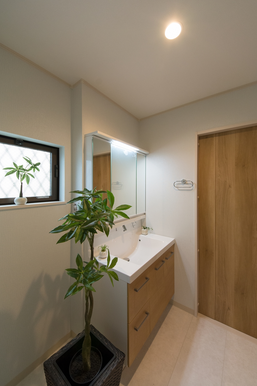木目調の洗面化粧台と建具がナチュラルな雰囲気の空間を演出。