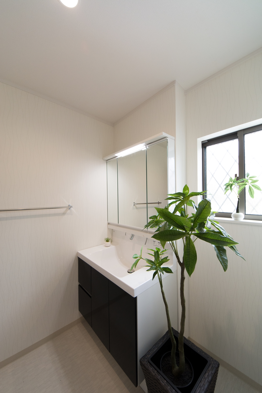 白を基調とした清潔感のあるサニタリールーム。ディープグレーの洗面化粧台がエレガントな雰囲気を演出。