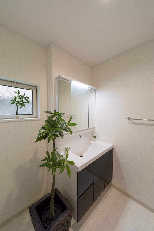 白を基調とした清潔感のあるサニタリールームディープグレーの洗面化粧台がエレガントな雰囲気を演出。