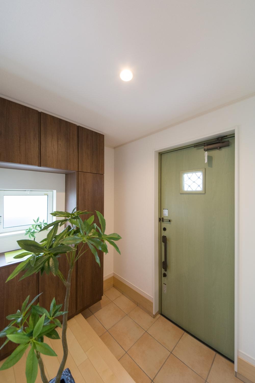 アースカラーでナチュラルな印象の玄関ホール。グリーンのドア、ブラウンの収納、ベージュ色タイルの組合せがマッチ。